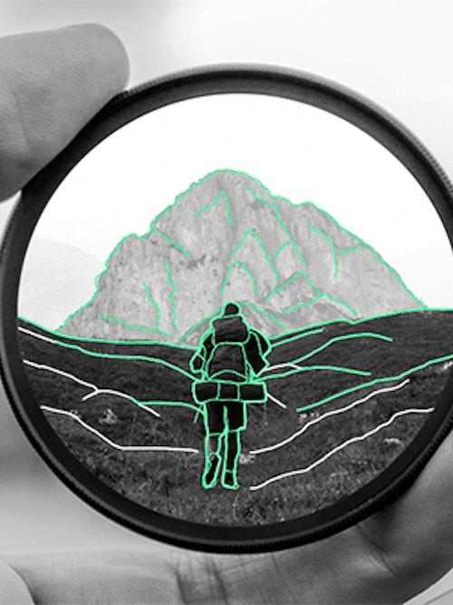 Illustrasjon av en linse som holdes i en hånd. I linsen ser man et fjell og en person som går tur.