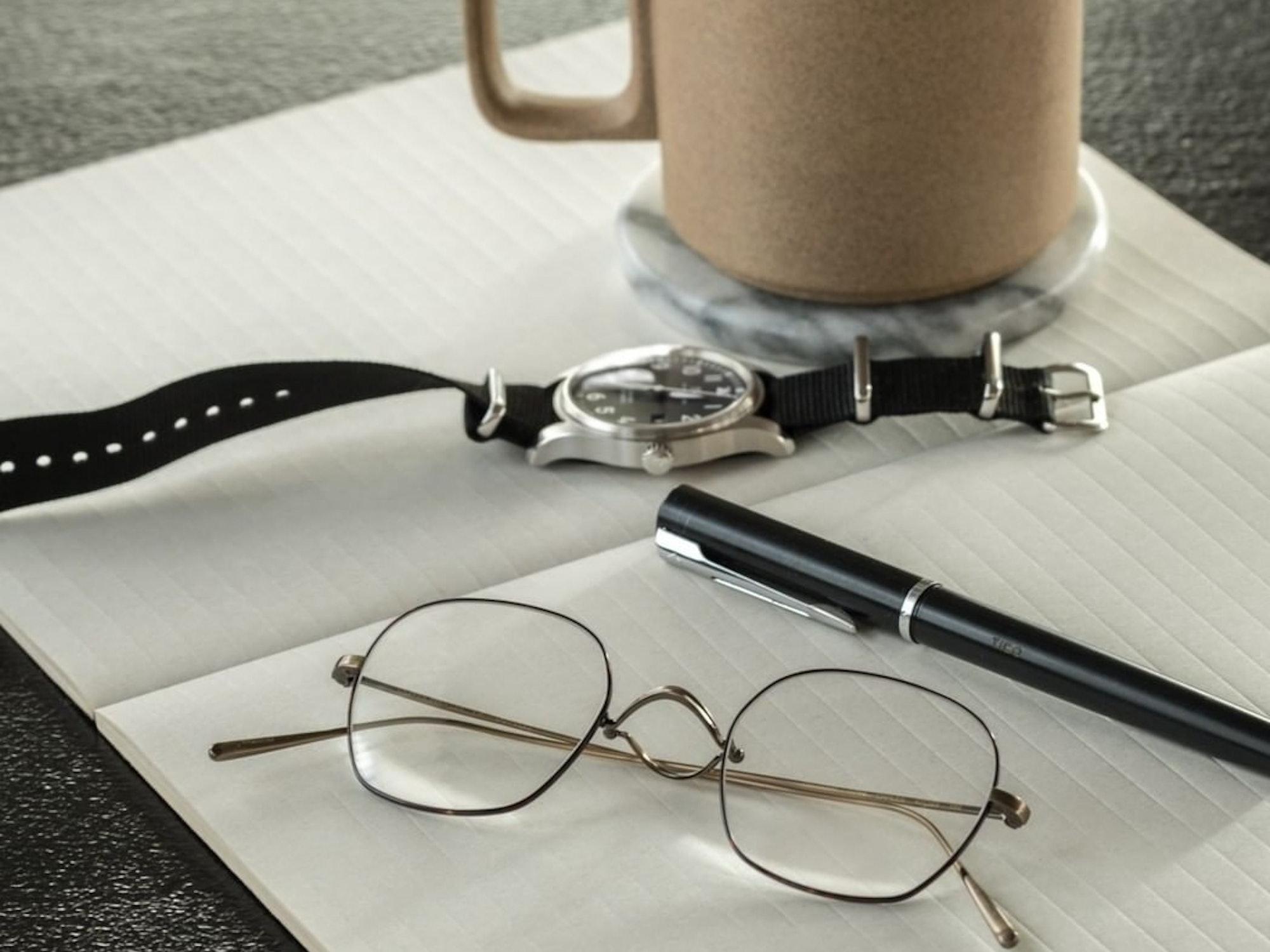 Bilde av en metallinnfatning fra Krogh Optikk som ligger på en bok sammen med klokke, penn og en kaffekopp.