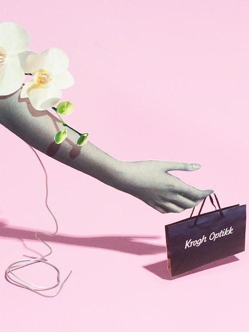 Bilde av en hånd som holder en Krogh Optikk-bærepose